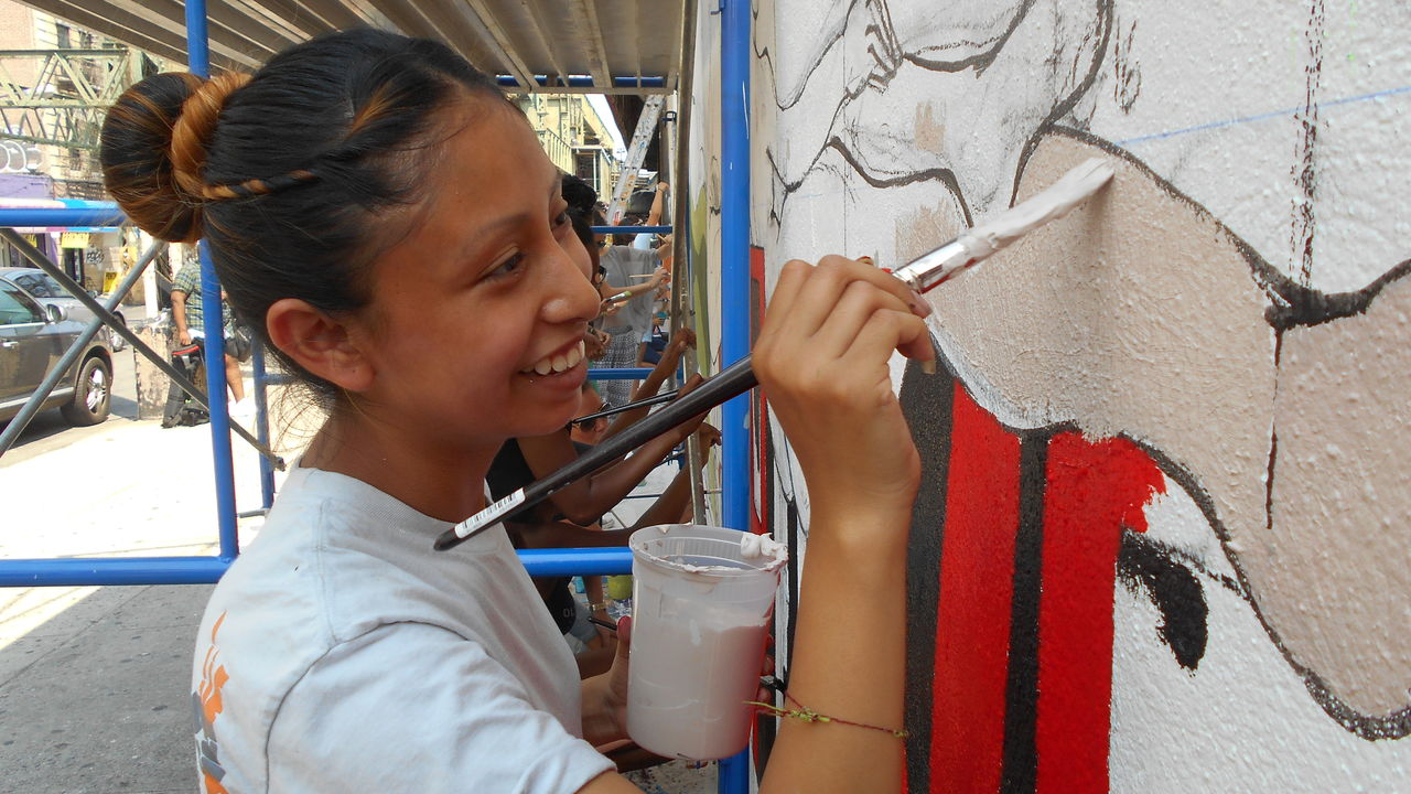 A young woman smiles as she paints a vibrant mural.