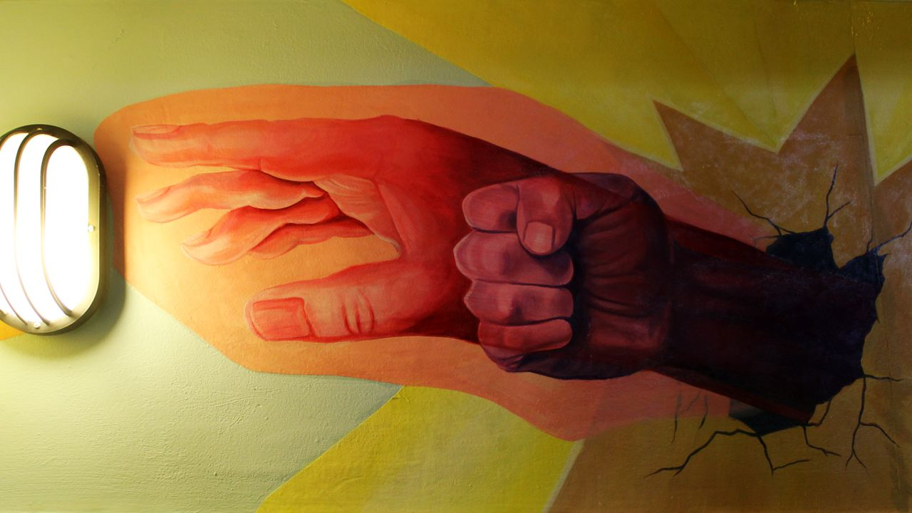 A mural sections shows a hand reaching toward a light.