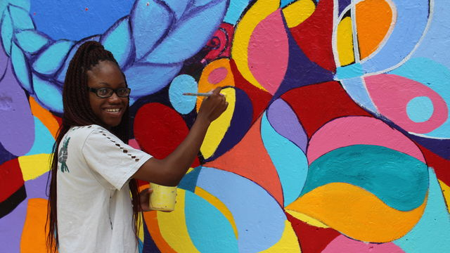 A young artist holds a paintbrush up to a vibrant, abstract mural.