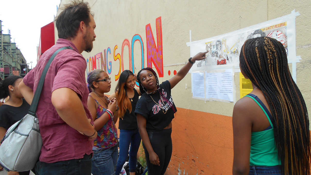 A young artist points to a mural design as she explains the symbols to a community member.