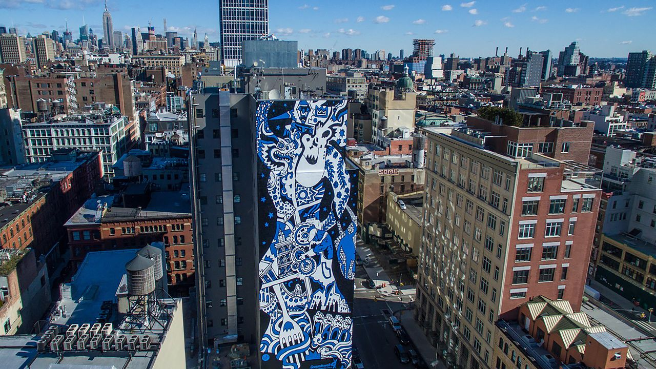 "The blue and white figure at the center of ""The Spirit of SoHo"" stands tall in this mural located in downtown Manhattan."