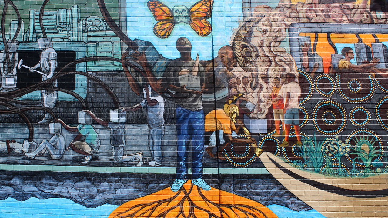 This mural section features a young man becoming empowered by reclaiming community resources.