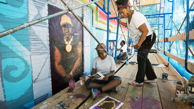 A teaching artists advises a student on how to use a sketch to paint a mural.