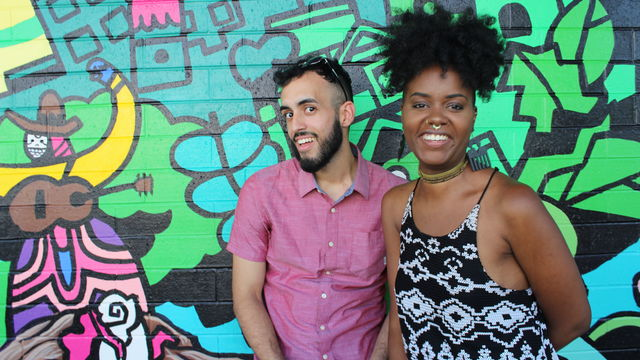 Two artists smile radiantly as they stand in front of a colorful mural.