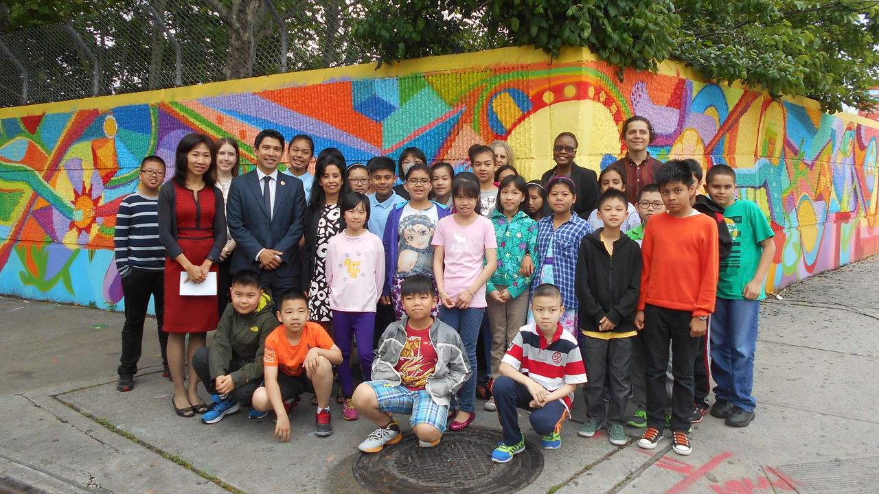 A group of elementary students and their teachers stand in front of a colorful mural they completed.