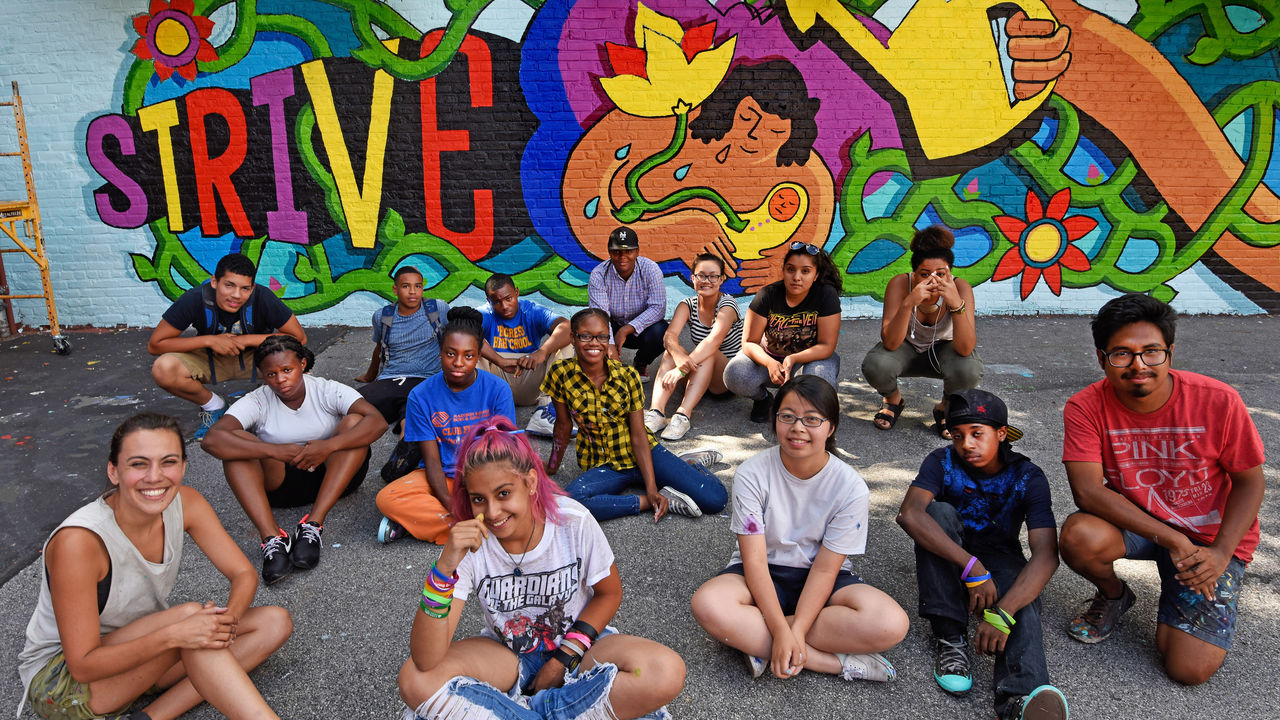A group of youth artists post in front of a vibrant mural.