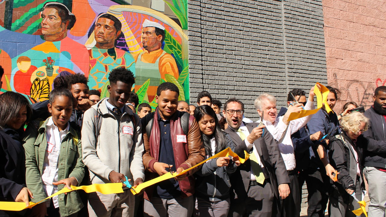 Students gather in front of a colorful mural during a dedication ribbon cutting.