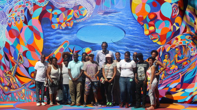 A Groundswell team stands in front of a vibrant mural painted on a handball court.