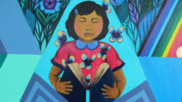 This mural detail features a young girl opening a book in front of a geometric background.