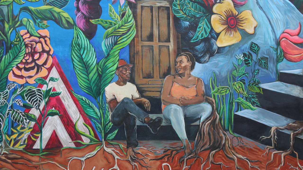 This mural detail features two women sitting on a stoop, surrounded by flowers.