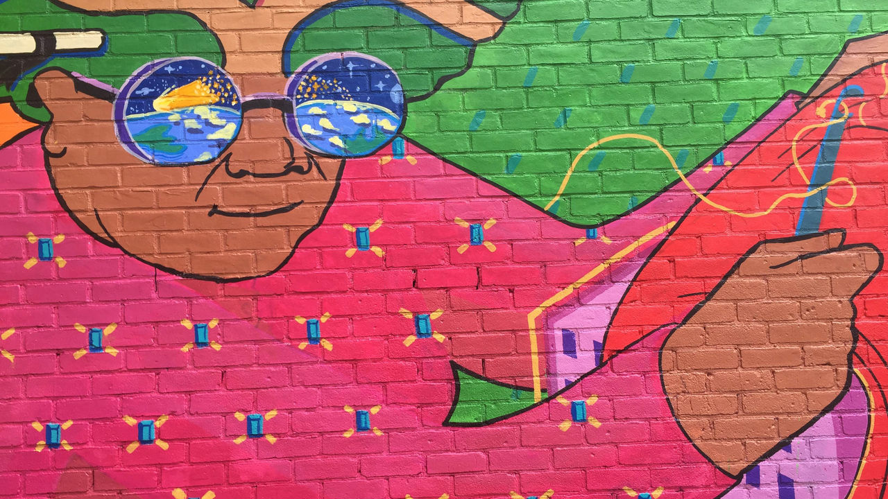 This mural detail features an old woman in a bright pink sweater knitting.