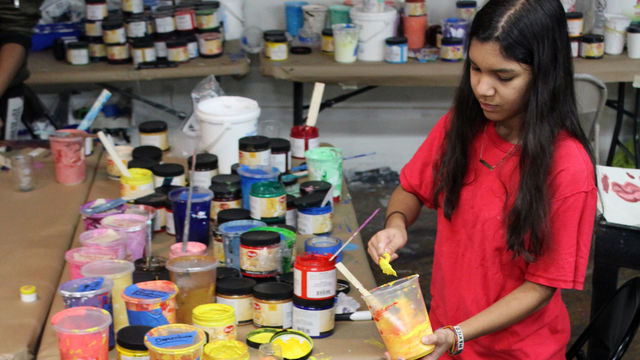 A youth artist mixes a wide selection of paints.