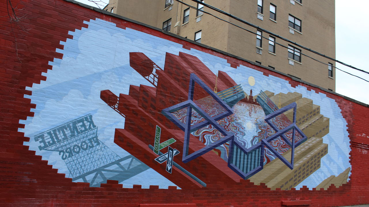 This wide shot of a mural features a geometric representation of the Gowanus Canal.