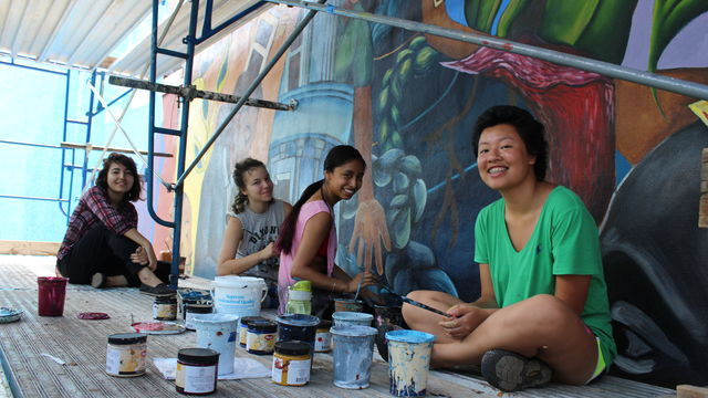 A group of young artists sit together on scaffolding, getting ready to paint a mural.