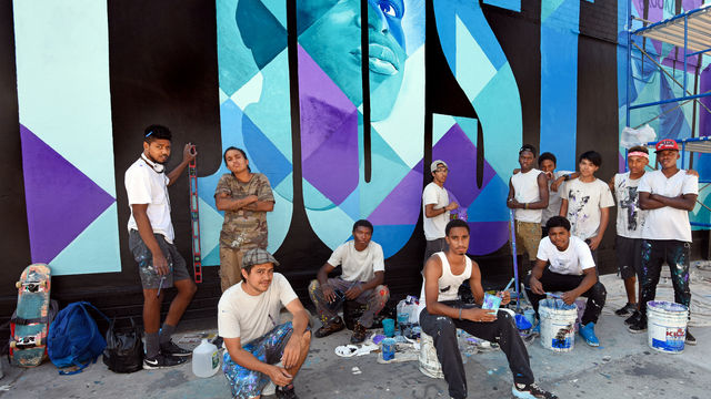 A group of young men stand confidently in front of a bright blue mural.