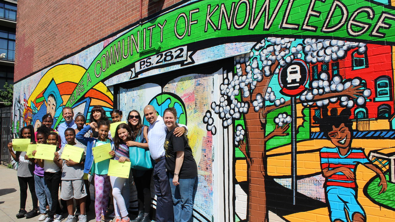 "A team of elementary students stand in front of a mural that declares ""We Are A Community of Knowledge."""