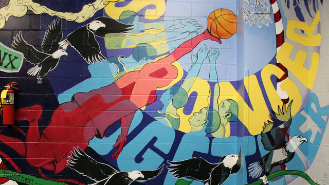 This mural detail features a youth people working together to slam dunk a basketball.