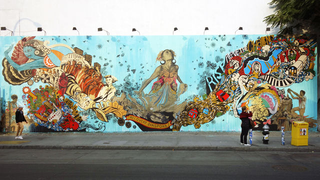 This wide view of a mural features a woman breaking through a tide of hope and resilience.