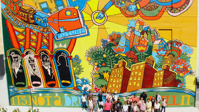 The artist team stands in front of their monumental mural celebrating Brownsville.