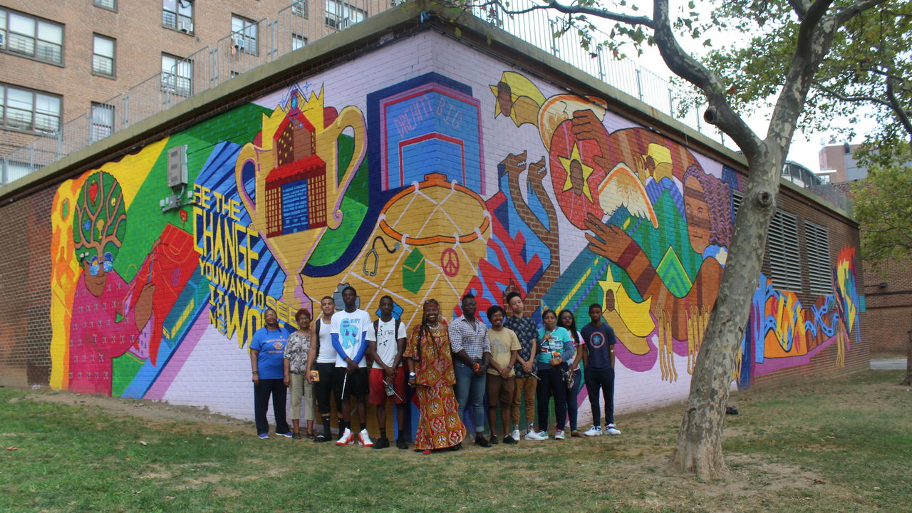 "The mural team stands proudly in front of a mural that declares ""Be The Change You Want To See In The World."""