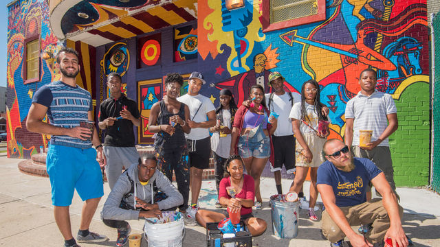 The artist team stands in front of a colorful mural that covers the entire front of an elementary school.