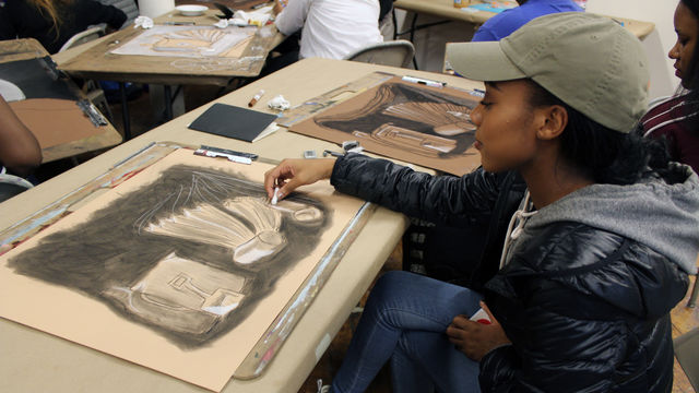 A young artist sketches a still life drawing.