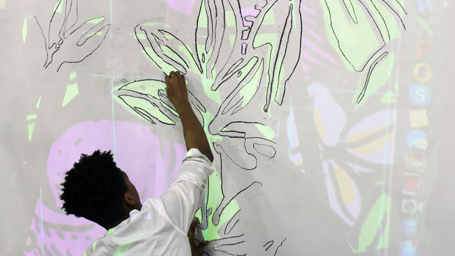 A young man uses a projector to transfer the mural design onto a canvas.