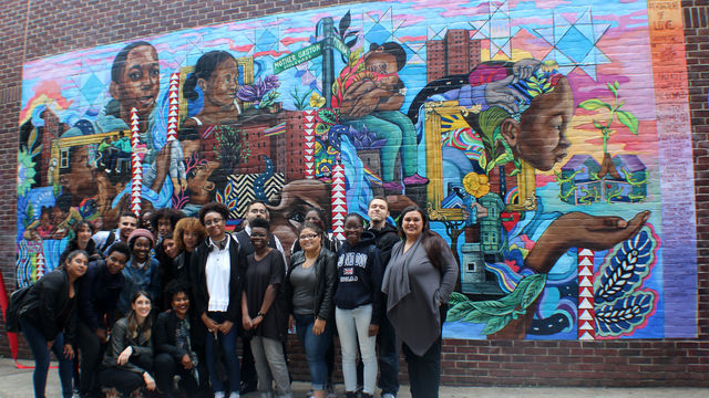 The mural team stands in front of a mural celebrating healthy families in Brownsville.