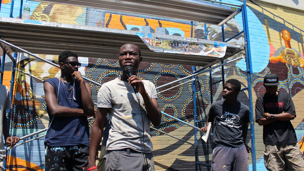 Speaking into a microphone, a young man proudly explains his team's mural.