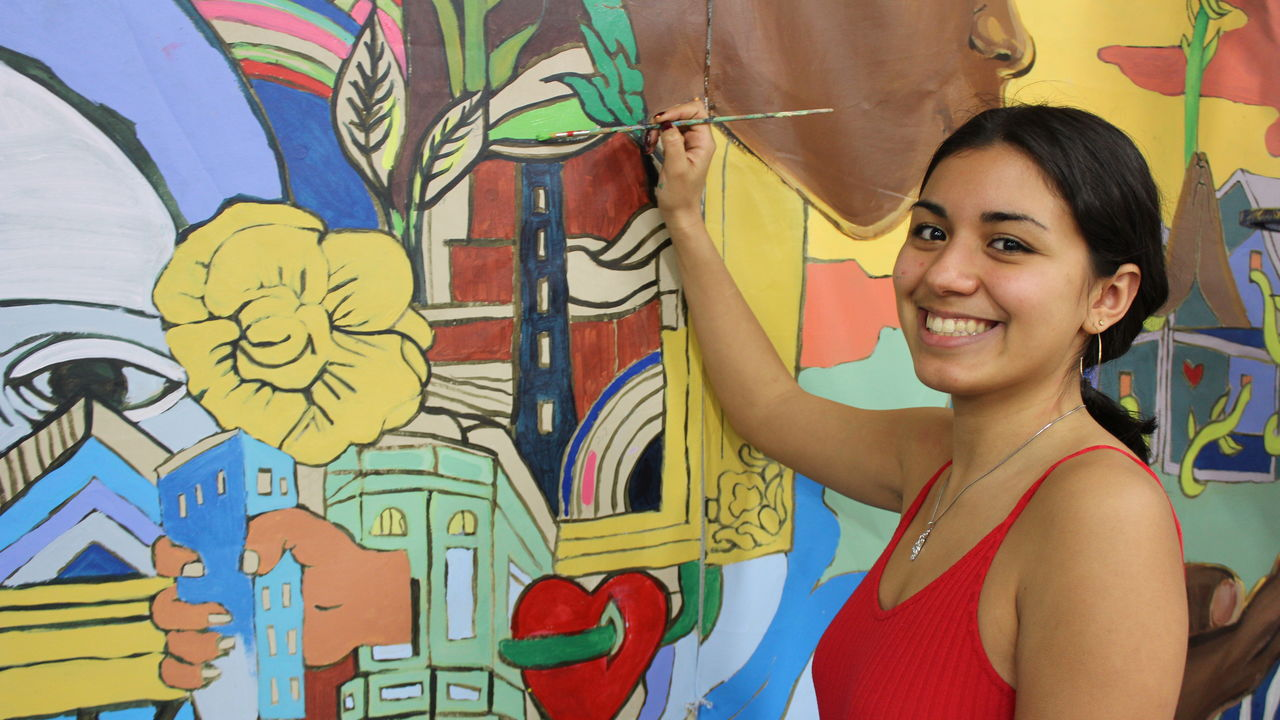 A youth artist holds a paintbrush to a colorful mural.