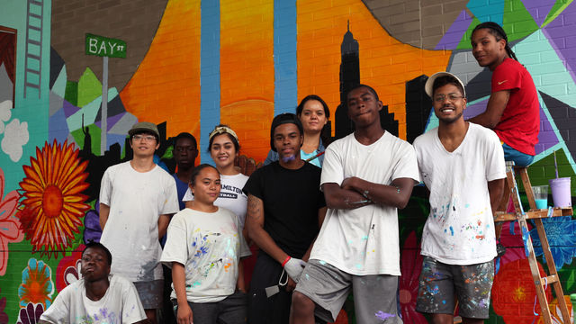 A mural team stands proudly in front of their mural celebrating their Staten Island community.