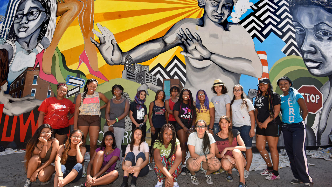 A group of young women stand confidently in front of their anti-street harassment mural.