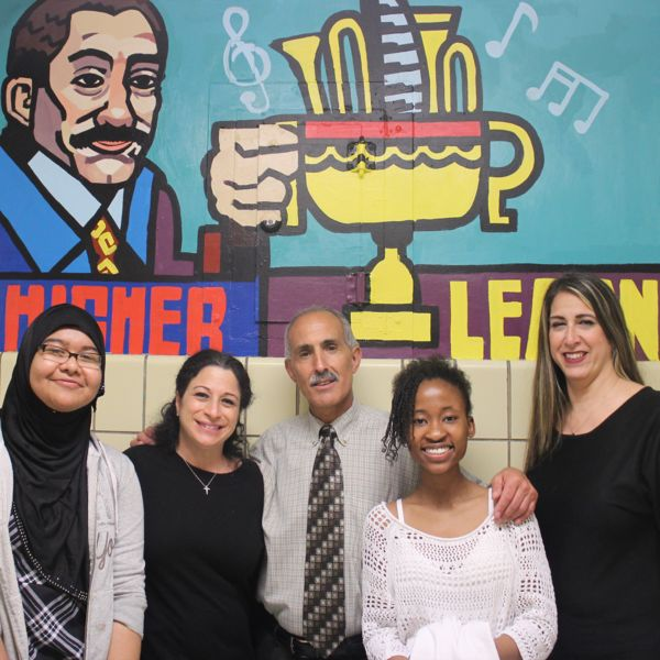 Youth, artists, and IS 62 educators celebrate the completion of a mural.