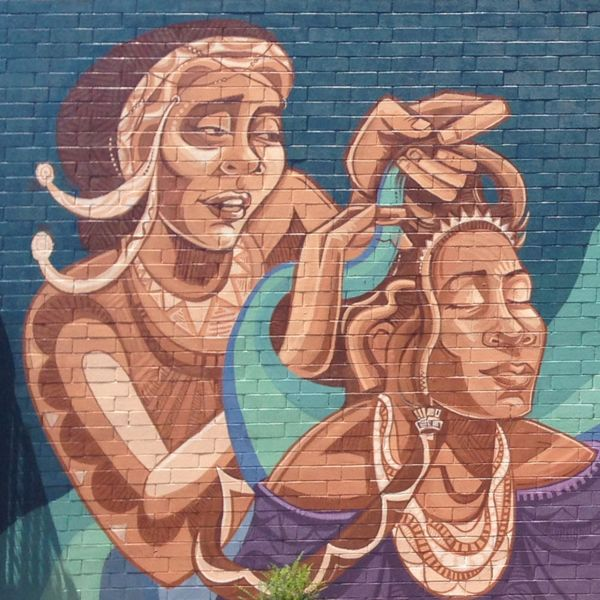 Mural detail shows a woman braiding another woman's hair.