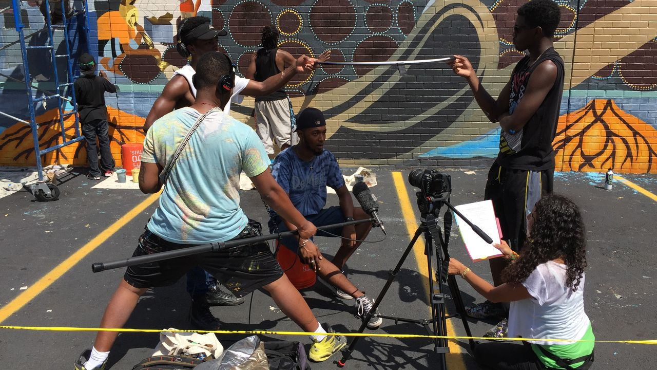 A reporter interview a youth artist in front of a mural.