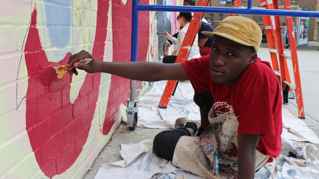 A young man sits down as he paints a mural.