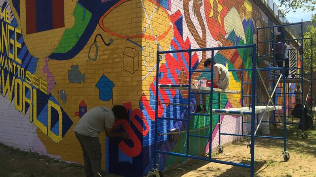 Teens paint a large wall with colorful designs.